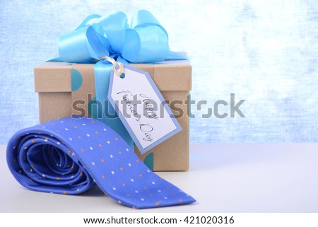 Happy Fathers Day gift and necktie on white wood table and pale blue background.