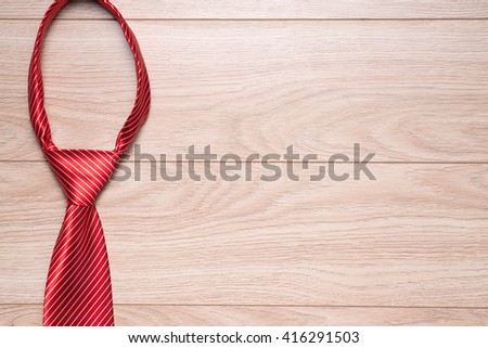 Happy Fathers Day gift tag with red striped necktie on rustic wood background