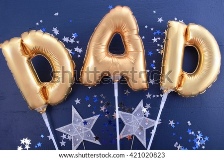 Happy Fathers Day gold balloons for the word, Dad, on dark blue wood background with silver and blue scattered glitter stars.