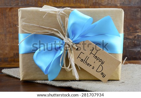 Happy Fathers Day natural kraft paper wrapped gift with pale blue ribbon on dark wood background.
