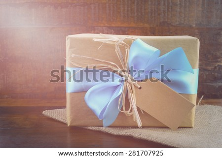 Happy Fathers Day, or masculine birthday, natural kraft paper wrapped gift with pale blue ribbon on dark wood background, with applied filters and added lens flare light stream.