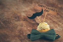 Happy fathers day special cupcake and bow tie on wooden table
