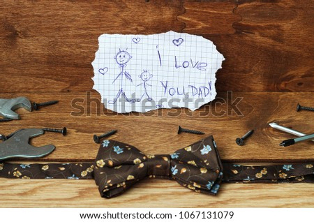 Happy Fathers Day with tools on a rustic wood background. Greeting card with Father's Day. View from above. Fathers day composition on wooden desk backround.  #1067131079