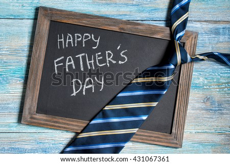 Happy Fathers Day written on chalkboard with blue striped tie on wooden background