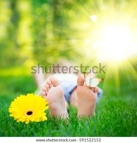 Shutterstock Happy feet with butterfly outdoors. Kid having fun in spring park. Child lying on green grass