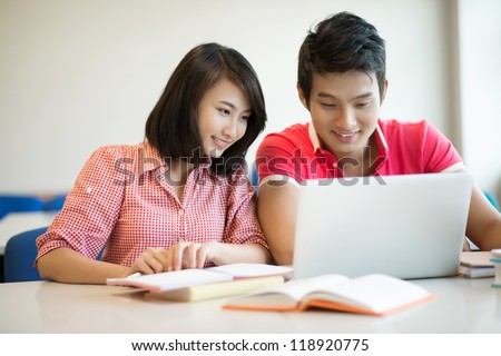 Happy fellow students doing homework together using books and modern technology