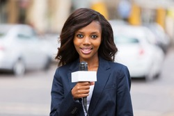 happy female african news reporter working outdoors