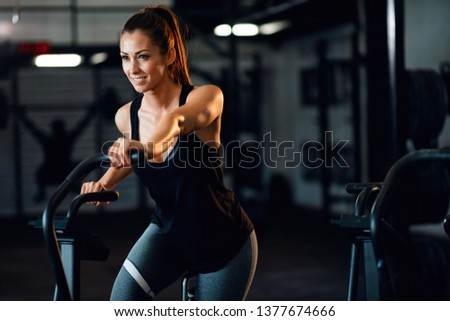 Happy female athlete exercising on stationary bike during her spinning class in a gym. Copy space. #1377674666