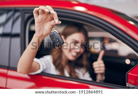 Happy female client smiling and gesturing thumb up while sitting in new vehicle and demonstrating keys in showroom