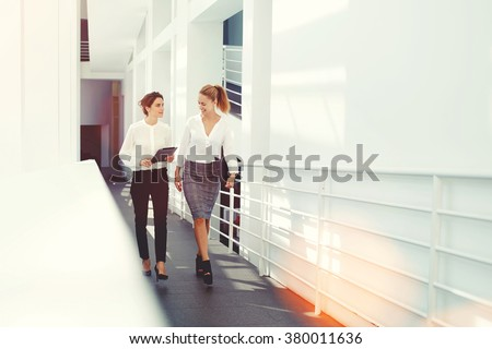 Happy female colleagues planning the schedule of work for next project via digital tablet while walking in office interior, women intelligent lawyers laughing at funny video on touch pad during break