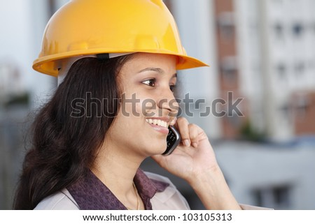 Happy female construction engineer talking on cellphone