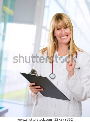 happy female doctor holding a clipboard against an abstract background