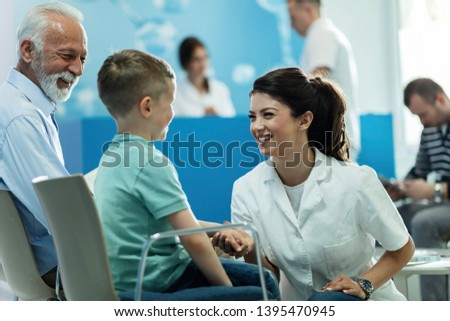 Happy female doctor talking to a small boy who came with grandfather for an medical appointment at clinic.