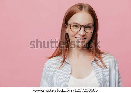 Happy female entrepreneur has straight hair, wears spectacles, smiles positively, enjoys good sales and profits, dressed in stylish shirt, models over pink background with copy space for your text #1259258605