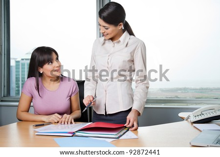 Happy female executives discussing business reports in office