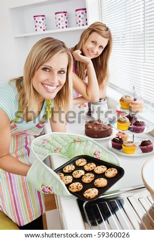 Happy female friends holding cookies in the kitchen at home