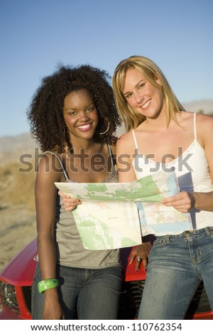 Happy female friends looking at map near car