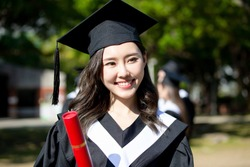 happy female graduate student holding diploma in her hand and smile