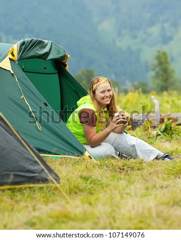 Happy female hiker drinking tea in front camp tent
