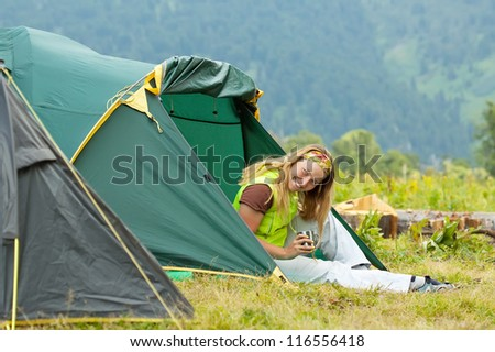 Happy female hiker in front of camp tent against mountains