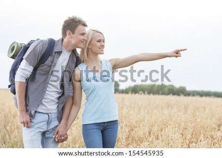 Happy female hiker showing something to man on field against clear sky #154545935