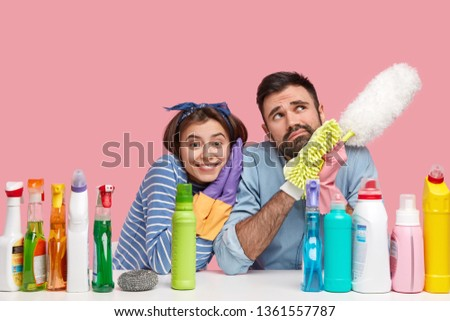 Happy female housekeeper leans at shoulder of thoughtful husband, cleans house together, do housekeeping, surrounded with cleaning detergents, hold mop, dust room have little rest after tired work. #1361557787