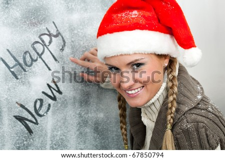 Happy female in Santa cap looking at camera while writing on frosty window