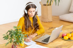 Happy female in wireless headphones studying online course, using pc and writing in notepad, copy space. Gig economy, digital nomad, distance education. Side view of mature woman work from home