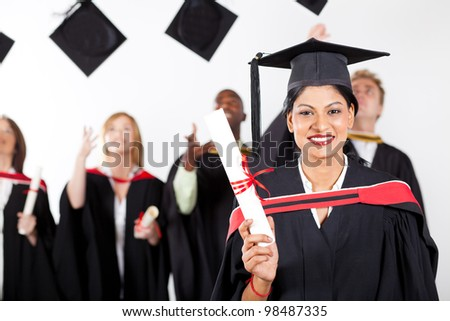 happy female indian graduate at graduation with classmates throwing caps