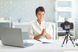 Happy female influencer and vlogger recording video for followers thanking them for support. Business woman making pre-recorded webinar in cozy office, sharing advice and motivating people for success