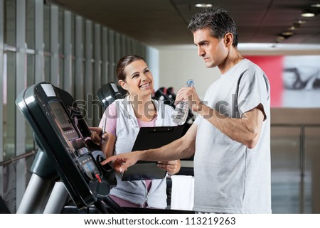Happy female instructor looking at male client on treadmill drinking water in health center