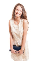 Happy female model smiling and holding her purse while wearing a lace dress isolated on white background
