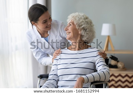 Happy female nurse or caregiver talk support positive handicapped old lady patient sitting in wheelchair in hospital, young woman doctor give help take care of mature handicapped grandmother