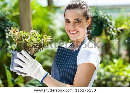 happy female nursery worker in greenhouse