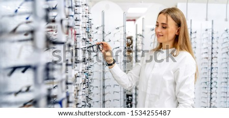 Happy female optometrist, optician is standing with many glasses in background in optical shop. Stand with spectacles. Eyesight correction.