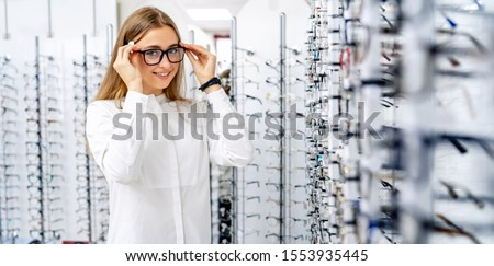 Happy female optometrist, optician is standing with many glasses in background in optical shop. Woman in spectacles in optics. Eyesight correction.