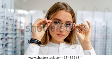 Happy female optometrist, optician is standing with set of glasses in background in optical shop. Stand with spectacles. Girl wearing glasses. Portrait of a woman in correcting glasses. Foto stock ©