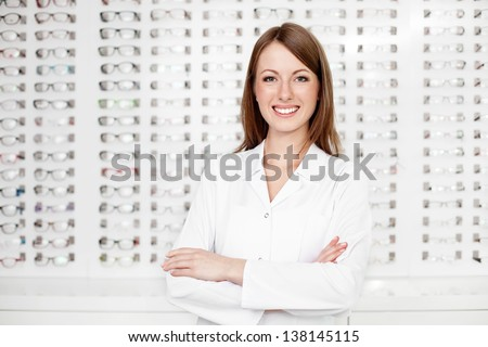 Happy female optometrist, optician standing  with many glasses in background in optical shop