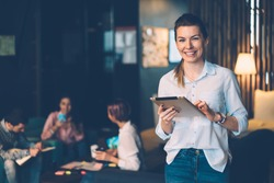 Happy female owner of successful business idea standing with digital tablet connected to wifi in office, portrait of prosperous smiling female entrepreneur satisfied of being leader of working team