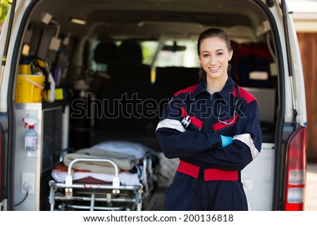 happy female paramedic standing in front of ambulance
