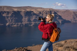 happy female photographer in warm coat with backpack and digital photo camera taking picture of river with high rocky shores while spending vacation on edge of cliff in United States of America