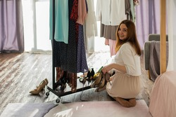 Happy female putting shoes and clothes on shelf at dressing room. Smiling woman organizing clothing and footwear and placing on rack. Organization storage of clothing. Accurate keeping outerwear