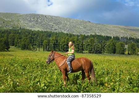 Happy female rider riding a horse bareback at mountains