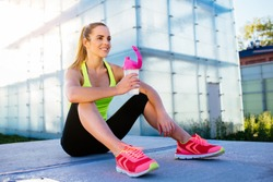 Happy female runner resting with bottle of water