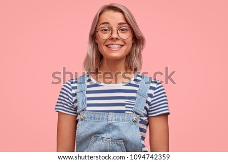 Happy female shop assistant, smiles politely, demonstrates white teeth with braces, talks with customer and offers help, stands against pink background, wears casual striped t shirt and denim overalls #1094742359