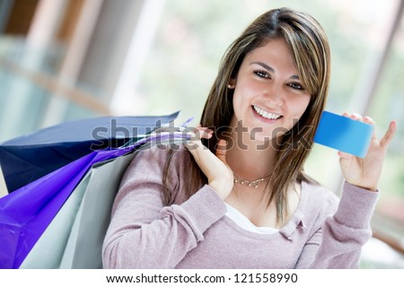 Happy female shopper holding a credit card and smiling