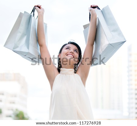 Happy female shopper with arms up holding shopping bags