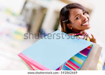 Happy female shopper with shopping bags and smiling
