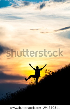 Happy female silhouette making funny dance. Woman making dancing moves on steep grassy hill with gorgeous sunset sky and cloudscape on background