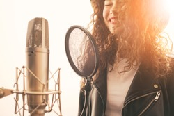 Happy female singer recording vocals
